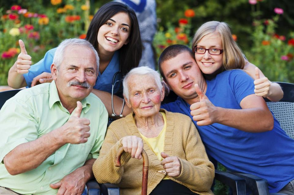 group of elderly and caregiver doing a thumbs up